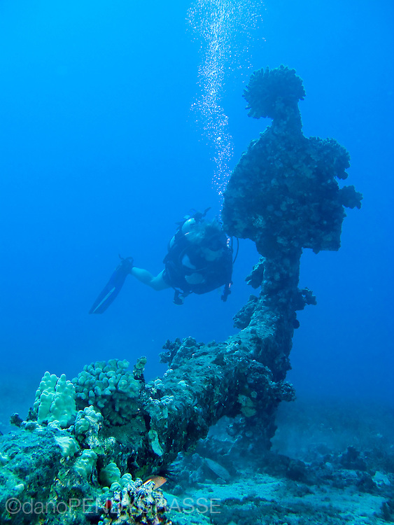 A scuba diver inspects an old Navy anchor near Maui, Hawaii, USA.