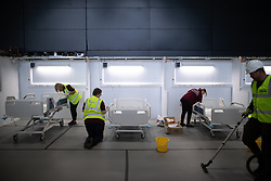 © Licensed to London News Pictures. 12/04/2020. Manchester, UK. Cleaners working on one of the wards . The National Health Service is building a 648 bed field hospital for the treatment of Covid-19 patients , at the historical railway station terminus which now forms the main hall of the Manchester Central Convention Centre . The facility is due to open on Easter Monday , 13th April 2020 , and will treat patients from across the North West of England , providing them with general medical care and oxygen therapy after discharge from Intensive Care Units . Photo credit: Joel Goodman/LNP