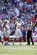 New York Giants cornerback Prince Amukamara (20) gets a pat on the helmet from a teammate after recovering a late fourth quarter fumble that effectively ices the win during the 2015 NFL week 4 regular season football game against the Buffalo Bills on Sunday, Oct. 4, 2015 in Orchard Park, N.Y. The Giants won the game 24-10. (©Paul Anthony Spinelli)