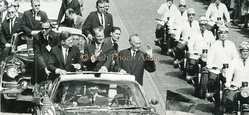 John F Kennedy (1917-1963) President of the USA, Willy Brandt (1913-1992)  and Konrad Adenauer (1876-1967) Chancellor of West Germany travelling in Berlin in an open car and acknowledging cheers from the crowd during the President's visit to the Federal German Republic, 26 June 1963.