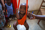 A young boy is being weighed during a community outreach vaccination session in Bela Vista, Mozambique.