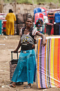 A woman with a mattress and a suitcase she bought during a non-food item fair at the Miketo IDP settlement, Katanga province, Democratic Republic of Congo on Sunday February 19, 2012. Displaced people who have lost most of their belongings as they fleed their homes receive coupons their can exchange for goods at a fair held in partnership with local traders.