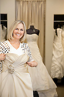 Portrait of a happy senior woman holding wedding gown in bridal store