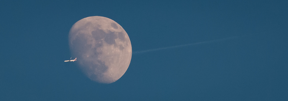 A jetliner passes directly in front of the moon off Fowler Beach, Milford, Delaware.