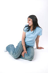 Portrait of a teenaged girl sitting on the floor smiling,