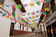 A pedestrian walkway decorated with colorful papel picado banners in Uruapan, Michoacan, Mexico.