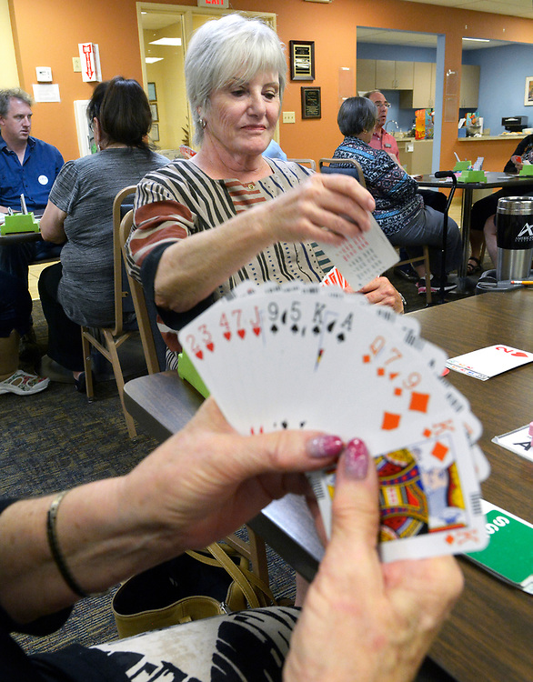 gbs062117a/ASEC -- Bliss Kelly-Loree of Albuquerque makes a play as Sue Berry holds her cards at the Duke City Bridge Club during a day-long fundraiser benefiting the local Alzheimers Association on Wednesday, June 21, 2017. The players were sponsored and the club also had a silent auction. (Greg Sorber/Albuquerque Journal)