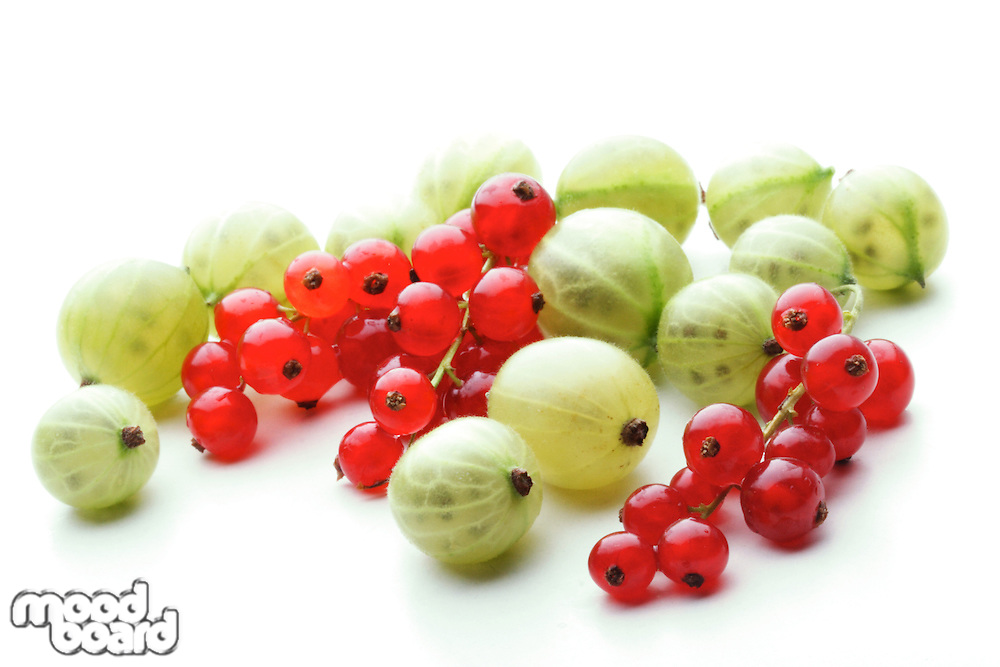 Gooseberries and redcurrants on white background