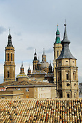 This is a bird's eye view of the tile roofs, church spires of the Basilica de Nuestra Senora del Pilar (Our Lady of the Pillar) and the tower of the Seo Cathedral in Zaragoza, Spain. The Cathedral of Our Lady of the Pillar was begun in 1681 and is constructed in the baroque style. The Feast of Our Lady of the Pillar celebrating the first apparition to the Hispanic People is celebrated on October 12, this coincides with the date that Columbus discovered the New World.  Zaragoza is located in the Province of Aragon.