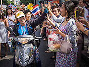 "29 NOVEMBER 2013 - BANGKOK, THAILAND: Office workers in Bangkok ""high five"" anti-government protestors as they motorcade through Bangkok. Although the government has a popular mandate, most of its supporters are from the rural northeast part of Thailand. Most members of Bangkok's middle class oppose the government. Several thousand Thai anti-government protestors marched on the US Embassy in Bangkok. They blew whistles and asked the US to honor their efforts to unseat the elected government of Yingluck Shinawatra. The anti-government protestors marched through several parts of Bangkok Friday paralyzing traffic but no clashes were reported, even after a group protestors tried to occupy Army headquarters.         PHOTO BY JACK KURTZ"