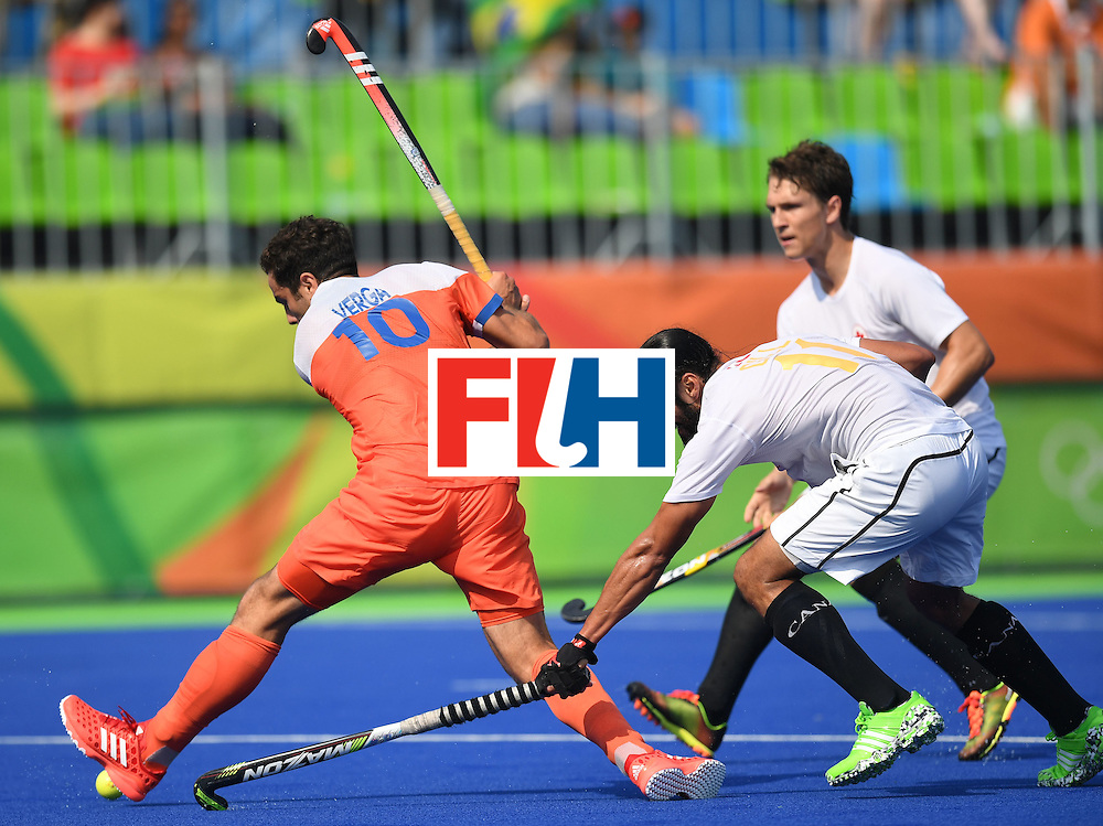 Netherland's Valentin Verga prepares to hit the ball as Canada's Jagdish Gill (C) reaches for it during the men's field hockey Netherlands vs Canada match of the Rio 2016 Olympics Games at the Olympic Hockey Centre in Rio de Janeiro on August, 9 2016. / AFP / MANAN VATSYAYANA        (Photo credit should read MANAN VATSYAYANA/AFP/Getty Images)