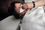 Nederland, Nijmegen, 26-4-2005Vrouw liogt ziek in bed en niest.Foto: Flip Franssen