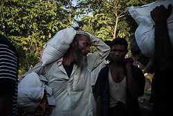 On the road, near Ukhia, Bangladesh. Refugees carry bags of rice to the camp.<br />