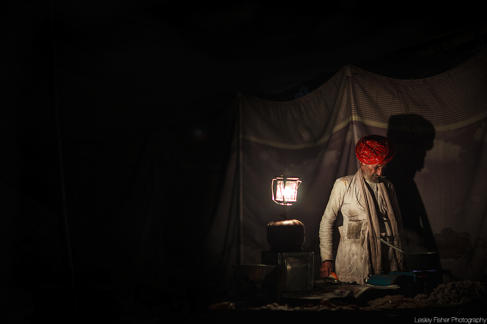 Chai seller preparing his chai in the early hours of the morning at the Pushkar Camel Fair, Rajasthan, India