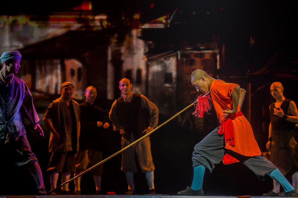 "A monk bends a spear while pushing the point against his neck - Twenty Shaolin monks, from their  temple in the foothills of the Song Shang mountain range in China's Henan province, take to the stage to demonstrate their martial arts expertise in an 'awe-inspiring' performance. SHAOLIN is a display of theatre and physical prowess in which the cast perform ""superhuman"" feats. The show combines traditional Shaolin Kung Fu, inch perfect choreography with dramatic lighting and sound that evokes the spirit of their tradition – their Temple being the birthplace of Kung Fu.  These are the very best Shaolin Kung Fu experts on the planet and they have come together to create this show. The Shaolin Monks are lifted aloft on sharpened spears, break marble slabs with their heads, perform handstands on two finger tips,splinter wooden staves with their bodies, break bricks on their heads and fly through the air in a series of incredible back flips. The show embarks upon a three-week run at The Peacock Theatre, London from 29 September – 17 October 2015."