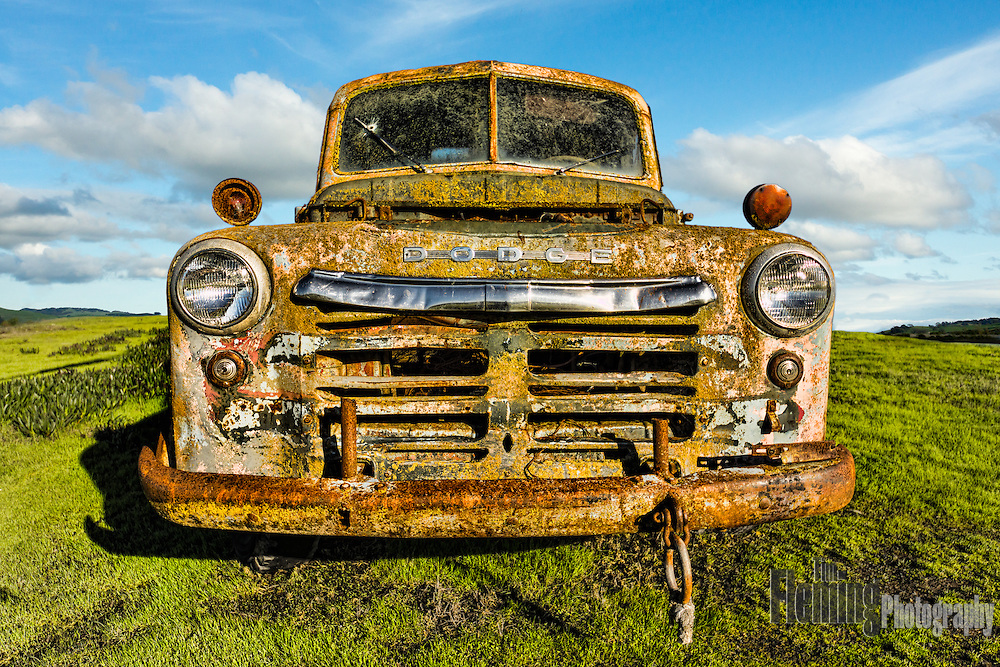 Old, aging truck in the middle of a field.