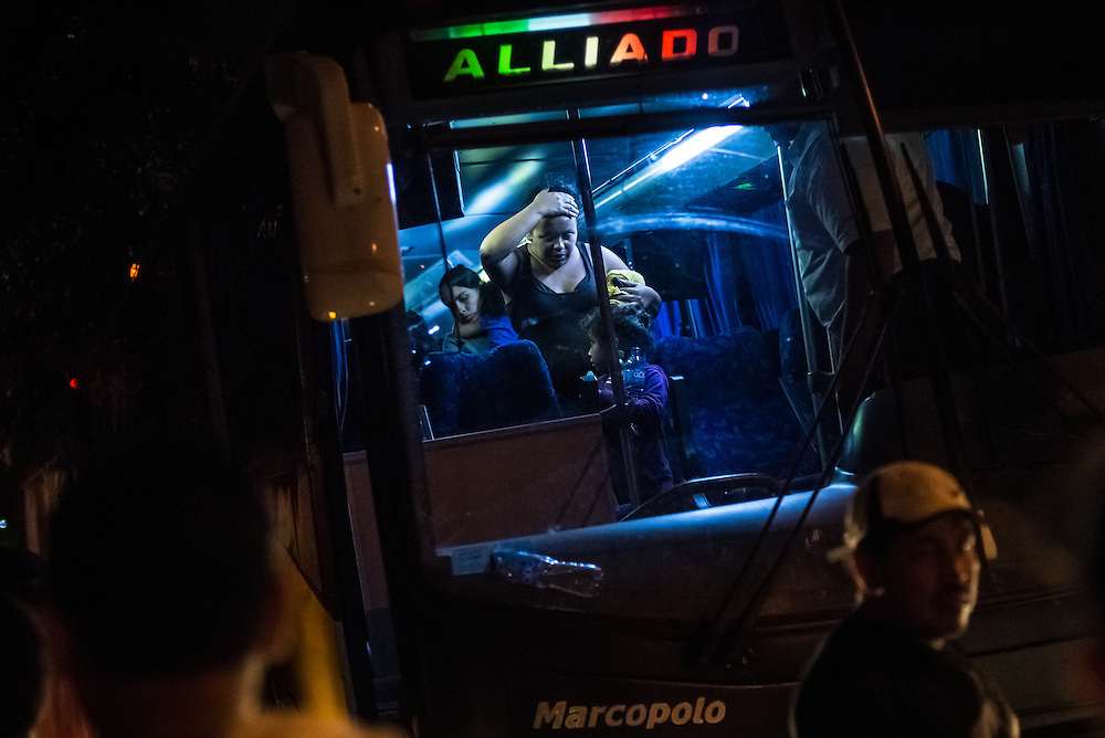 SAN PEDRO SULA, HONDURAS - MAY 22, 2014:  Families caught and deported arrive back in Honduras on buses full of deportees in San Pedro Sula. In recent months, authorities have noted a boom in child migrants arriving in the United States. PHOTO: Meridith Kohut for The New York Times