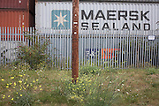 Maersk Sealand, P &O shipping container and security fence landscape at Tilbury Docks, Thames Gateway