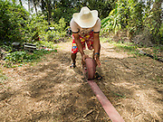 14 JULY 2015 - THAILAND:  A provincial water department worker rolls up a hose after delivering water to a homeowner (left) in Nakhon Nayok province. The drought that has crippled agriculture in central Thailand is now impacting residential areas near Bangkok. The Thai government is reporting that more than 250,000 homes in the provinces surrounding Bangkok have had their domestic water cut because the canals that supply water to local treatment plants were too low to feed the plants. Local government agencies and the Thai army are trucking water to impacted communities and homes. Roads in the area have started collapsing because of subsidence caused by the retreating waters. Central Thailand is contending with drought. By one estimate, about 80 percent of Thailand's agricultural land is in drought like conditions and farmers have been told to stop planting new acreage of rice, the area's principal cash crop.      PHOTO BY JACK KURTZ