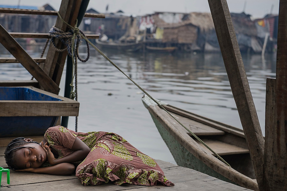 A girl sleeps on a jetty in Makoko