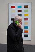A man holding his phone walks with a green case walks past a colour swatch on the wall of a central London business, on 22nd November 2017, in London England.