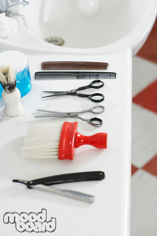 Scissors combs razor and brush on counter in barber shop