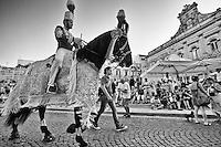 Ostuni Cavalcata S.Oronzo agosto 2012. Foto in bianco e nero che ritre cavallo e cavaliere nella piazza S.Oronzo..Sant'Oronzo si nascose anche in una grotta a Ostuni, nel luogo dove è stata poi costruita la chiesa e il relativo Santuario. I festeggiamenti si svolgono nella Città Bianca il 25, 26 e 27 agosto con la rinomata Cavalcata di Sant'Oronzo, una processione nella quale sfilano esponenti del clero e dell'amministrazione comunale, seguiti da cavalli e cavalieri, con stoffe rosse ricche di ricami e lustrini. I festeggiamenti comprendono anche due fiere e uno spettacolo di fuochi.