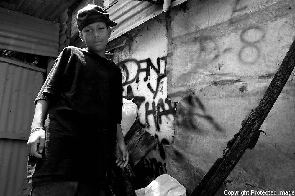 Kevin stands outside his home in the slum of San Felipe where he has tagged his name (Chara) and his brother's name (Dani) on the metal wall of his home.