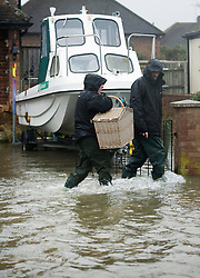 © London News Pictures. 12/02/2014. Egham, UK.  Residents of Egham in Surrey carrying a basket through flood water. Torrential rain in the area is due to raise water levels increasing the risk of further flooding. Photo credit : Ben Cawthra/LNP