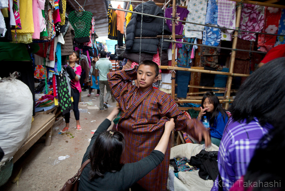 A mother fits traditional cloth to her son at the weekend market in Thimphu, Bhutan on September 1, 2013<br /> (Photo by Kuni Takahashi)