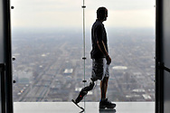 "Zac Vawter, fitted with an experimental ""bionic"" leg, poses for a portrait on the Ledge at the Willis Tower, Thursday, Oct. 25, 2012 in Chicago. Vawter is training for the world's tallest stair-climbing event where he'll attempt to climb 103 flights to the top of theWillis Tower using the new prosthesis.  (AP)"