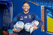 AFC Wimbledon goalkeeping coach Ashley Bayes holding footballs and smiling during the EFL Sky Bet League 1 match between AFC Wimbledon and Lincoln City at the Cherry Red Records Stadium, Kingston, England on 2 November 2019.
