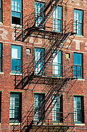 A fire escape casts shadows on the side of a converted warehouse in Omaha, Nebraska.