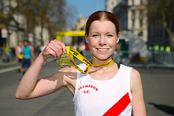 A competitir poses with her medal during the 2019 London Landmarks Half Marathon.