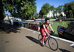 © Licensed to London News Pictures. 24/07/2018. London, UK. A cyclist makes her way along the canal towpath at Little Venice in central London, as warm temperatures in the capital continue. Forecasters are predicting record temperatures later this week. Photo credit: Ben Cawthra/LNP