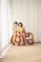 Mother and daughter (5-6) sitting in armchair reading book