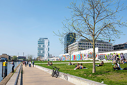 View of people in riverside park beside original section of Berlin Wall at East Side Gallery in Friedrichshain, Berlin, Germany