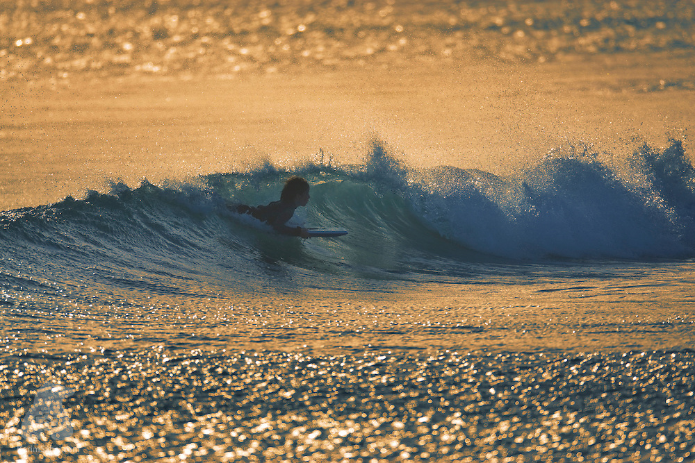 22 February 2009, Wellington, New Zealand. A bodyboarder catches a wave at Lyall Bay, at dusk.