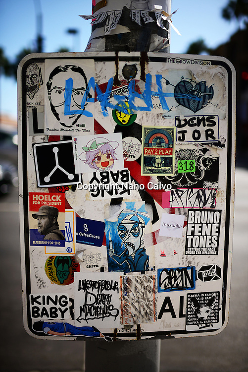 Assorted stickers in street sign, Los Angeles, California.