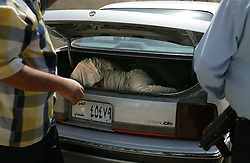 A suspect lies in the trunk of a car, after being arrested by Iraqi police outside the Al Dulaimi Hotel, Baghdad, Iraq, Aug. 4, 2003. Police searched for the kidnappers for 12 days resulting in the arrest of four people in connection with a kidnapping ring. Inside the home of two of the suspects, a woman and man  were found tied with restraints, as well as an undisclosed amount of cash and weapons. According to police, the kidnappers were asking for $5000 for the release of the victims. The woman appeared to have been tortured. Kidnapping has been on the rise as the city is still in chaos, Iraqi police are still in training with U.S. forces and continue to fight the increasing crime.