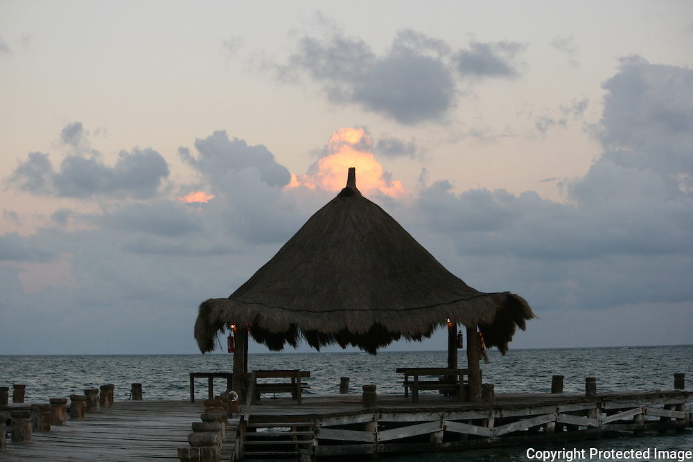 Boat dock and gazebo at Puerto Morelos at sunset.