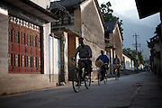 Three men ride their bicycles through the old Town of Dali China.