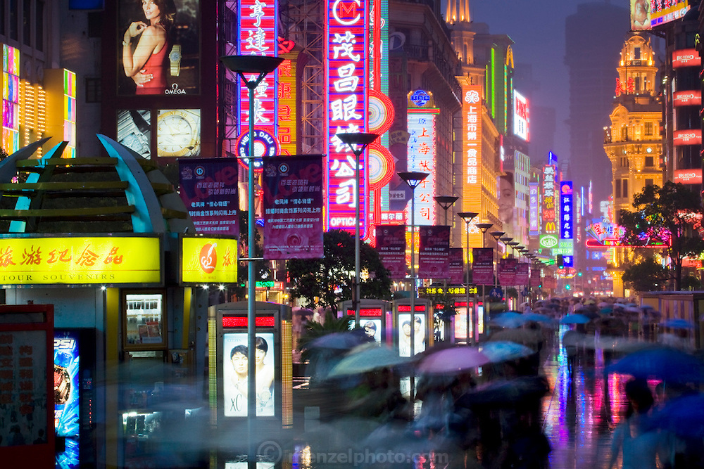 People huddle under umbrellas on a rainy evening in Shanghai, China.