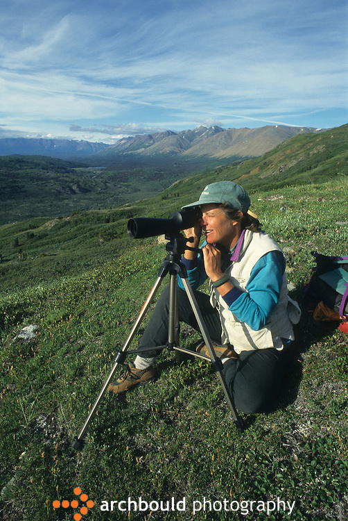 Woman looking through scope on Donjek Glacier hike in Kluane National Park