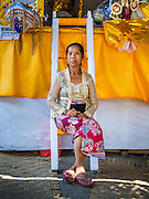 14 JULY 2016 - UBUD, BALI, INDONESIA: A woman sits on the ladder in front of her family's cremation alter in Ubud. The alter, with the remains of her family member, will be burned in a mass cremation Saturday. Local people in Ubud exhumed the remains of family members and burned their remains in a mass cremation ceremony Wednesday. Thursday was spent preparing for Saturday's ceremony that concludes the cremation. Almost 100 people will be cremated and laid to rest in the largest mass cremation in Bali in years this week. Most of the people on Bali are Hindus. Traditional cremations in Bali are very expensive, so communities usually hold one mass cremation approximately every five years. The cremation in Ubud will conclude Saturday, with a large community ceremony.     PHOTO BY JACK KURTZ