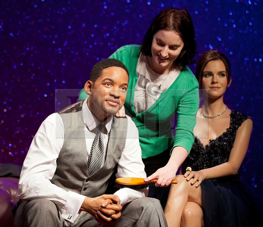 © Licensed to London News Pictures. 22/05/2013. London, UK. Wardrobe assistant, Luisa Compobassi brushes down a waxwork figure of rapper, actor and producer Will Smith after he was placed on a sofa alongside actor George Clooney (not shown) and Harry Potter actress Emma Watson. The former Fresh Prince of Bel Air star today (22/05/2013) took his place in Madame Tussauds 'A-List' party in London. Photo credit: Matt Cetti-Roberts/LNP
