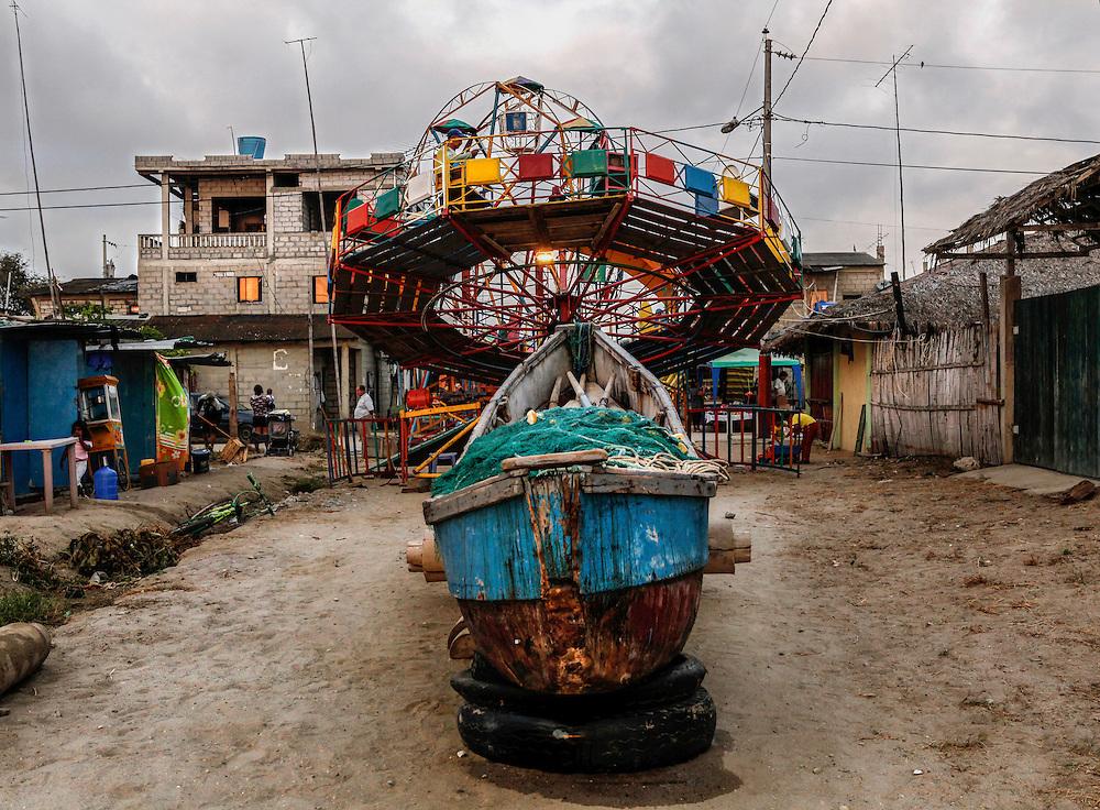Seg&uacute;n investigaciones antropol&oacute;gicas, hace miles de a&ntilde;os el valle de valdivia fue la cuna de una nueva civilizaci&oacute;n que forjo lo que hoy es sudam&eacute;rica. A pesar de ser uno de los primeros asentamientos humanos en el territorio ecuatoriano, su cultura, en el presente, se preserva en los l&iacute;mites de la modernidad. El trabajo agr&iacute;cola, la pesca y la peque&ntilde;a idustria artesanal y los saberes ancestrales, son el motor de desarrollo de esta regi&oacute;n de la costa ecuatoriana donde su cotidianidad transcurre en creencias de mitos y leyendas como un letargo del pasado. <br /> Foto: Detr&aacute;s de una barca de pesca artesanal, en una calle central de la Comuna de Valdivia, una feria de juegos infantiles se prerpara para la fiesta en homenaje a la virgen Nuestra Se&ntilde;ora de la Esperanza.
