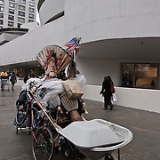 A man heavily loaded passing in front of the Guggenheim museum.