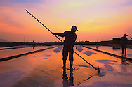 Vietnamese farmers work at dawn in a salt marsh of Doc Let, Khanh Hoa Province, Vietnam, Southeast Asia