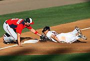 Mar 21, 2013; Lake Buena Vista, FL, USA; Atlanta Braves shortstop Andrelton Simmons (19) is caught stealing as Washington Nationals third baseman Ryan Zimmerman (11) makes the tag at Champion Stadium.